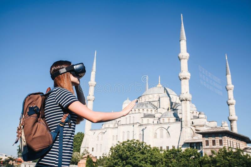 Un viaggiatore con i vetri di realtà virtuale Il concetto del viaggio virtuale intorno al mondo Nei precedenti il blu immagini stock