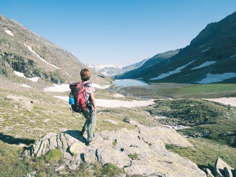 Un viaggiatore con zaino e sacco a pelo della persona che esamina vista alta su sulle alpi Paesaggio di Expasive, vista idilliaca immagine stock