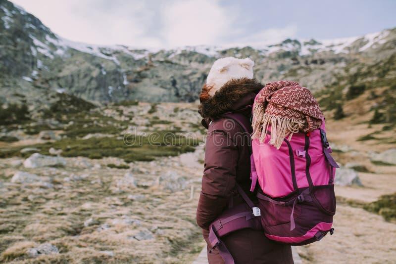 Un viaggiatore con zaino e sacco a pelo esamina la montagna da una valle enorme immagine stock libera da diritti