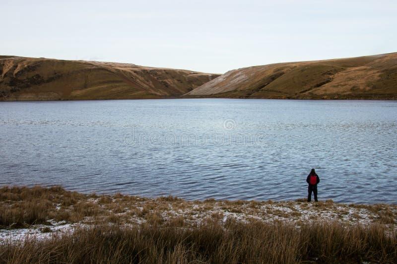 Un viaggiatore con zaino e sacco a pelo solo che sta sull'orlo di un bacino idrico che guarda fuori sulla brughiera brulla nell'i fotografie stock libere da diritti