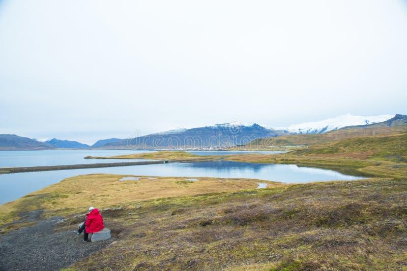 Un viaggiatore di signora che si siede sulle rocce lungo la strada sta esaminando la t fotografia stock