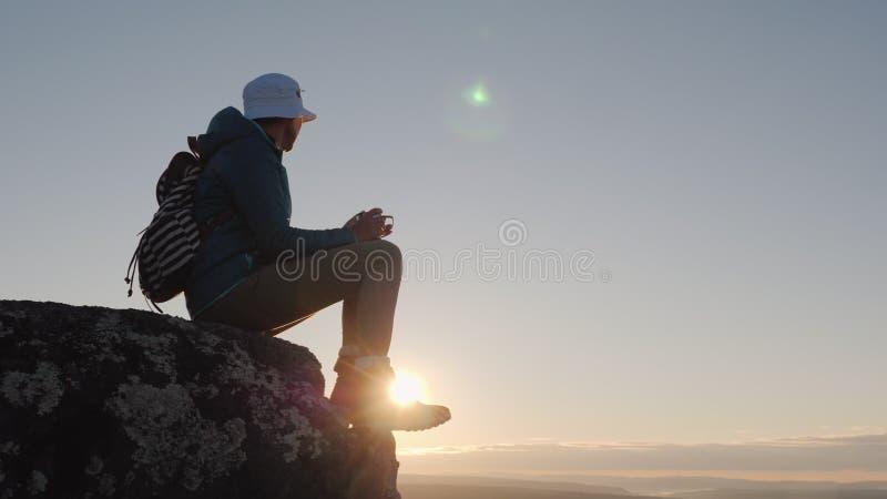 Un viajero bebe té de una taza en el pico de la montaña Se sienta en una roca, en el fondo un cielo rojo y cielo lejos foto de archivo libre de regalías