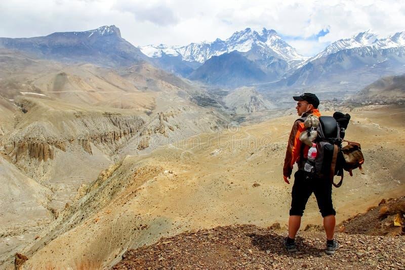 Un viajero con una mochila en las montañas Himalayan mira la garganta nepal Reino del mustango superior foto de archivo