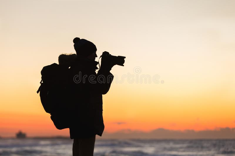 Un viajero con una mochila se está colocando en la costa y está fotografiando la salida del sol imagenes de archivo