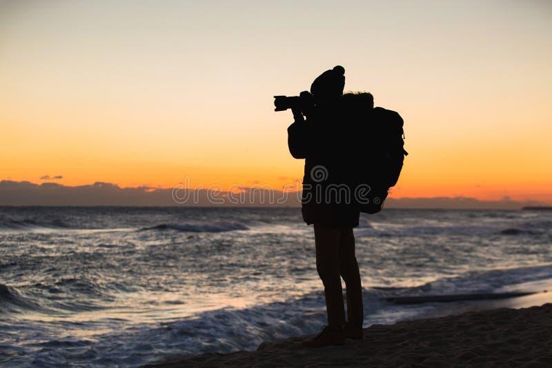 Un viajero con una mochila se está colocando en la costa y está fotografiando la salida del sol imagen de archivo