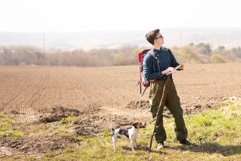 Un viajero con una mochila y su perro, mirando el mapa y caminando en el campo foto de archivo