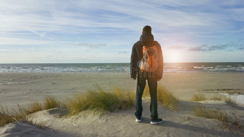 Un viajero del hombre joven con una mochila se coloca en la playa y admira la visión Pensamiento en el futuro solamente Luz hermo imágenes de archivo libres de regalías