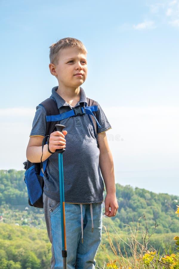 Un viajero del muchacho con emigrar polos y una mochila se coloca encima de una monta?a entre bosque verde imagen de archivo libre de regalías