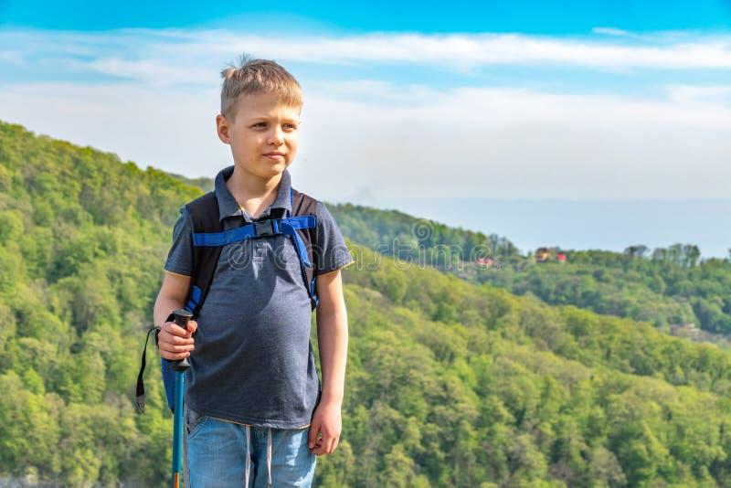 Un viajero del muchacho con emigrar polos y una mochila se coloca encima de una monta?a entre bosque verde fotos de archivo