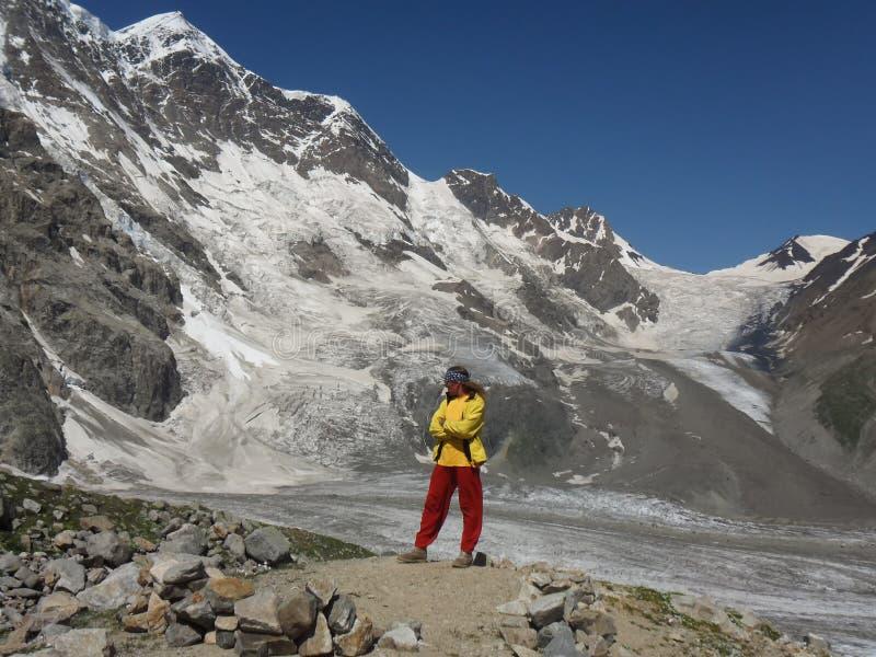 Un viajero en ropa brillante se coloca enfrente de las montañas grandes del hielo foto de archivo