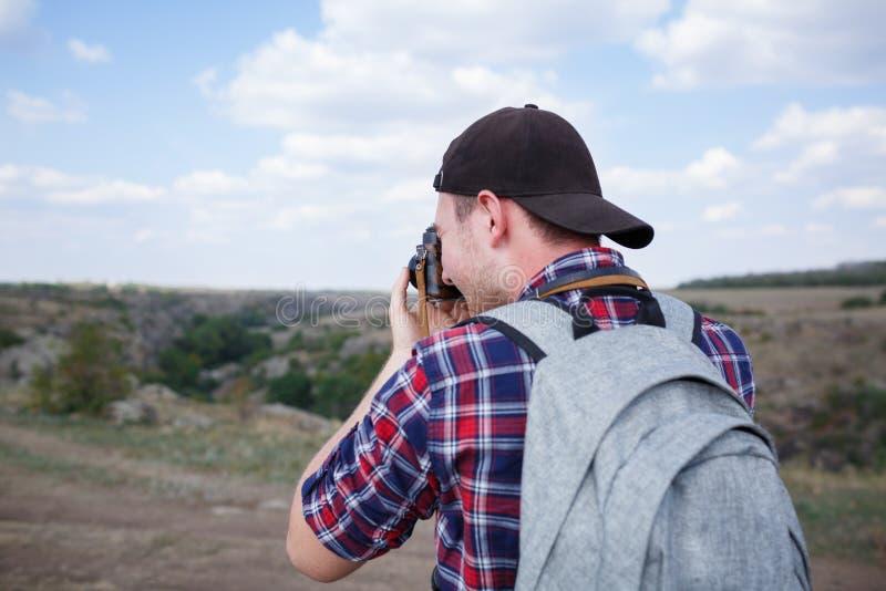 Un viajero en una camisa de tela escocesa subió para arriba una montaña y disfrutó de la visión Viaje del verano a las montañas imagenes de archivo