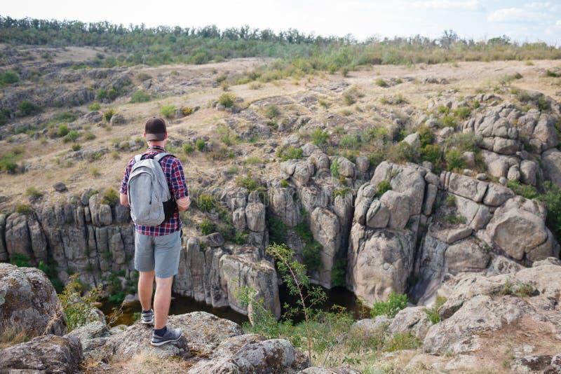 Un viajero en una camisa de tela escocesa subió para arriba una montaña y disfrutó de la visión Viaje del verano a las montañas fotografía de archivo libre de regalías