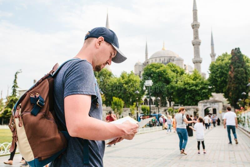 Un viajero en una gorra de béisbol con una mochila está mirando el mapa al lado de la mezquita azul - la vista famosa de fotografía de archivo libre de regalías
