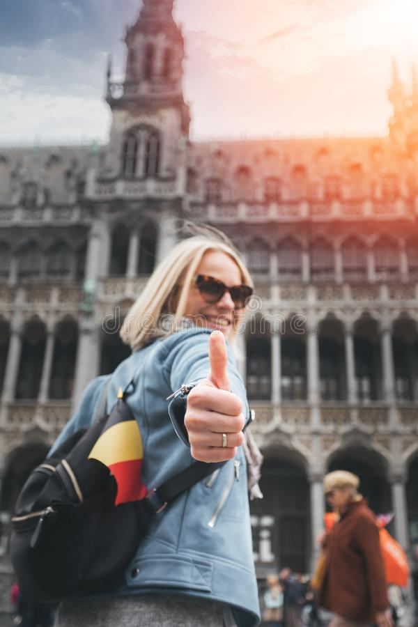 Un viajero femenino con una mochila y una bandera de Bélgica se coloca en el cuadrado de Grand Place en Bruselas y muestra sus pu imagen de archivo