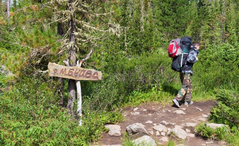 Un viajero masculino sano activo con dos mochilas va a caminar a lo largo de una trayectoria áspera en el día de verano soleado e fotos de archivo libres de regalías