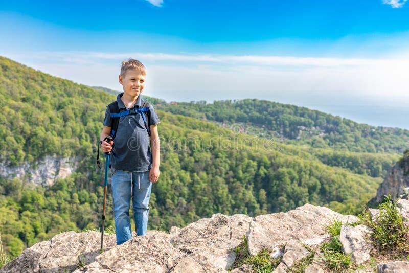 Un viajero sonriente del muchacho con emigrar polos y una mochila se coloca encima de una monta?a entre un bosque verde fotos de archivo libres de regalías