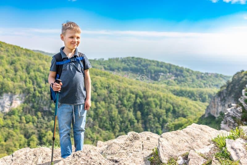 Un viajero sonriente del muchacho con emigrar polos y una mochila se coloca encima de una monta?a entre un bosque verde foto de archivo