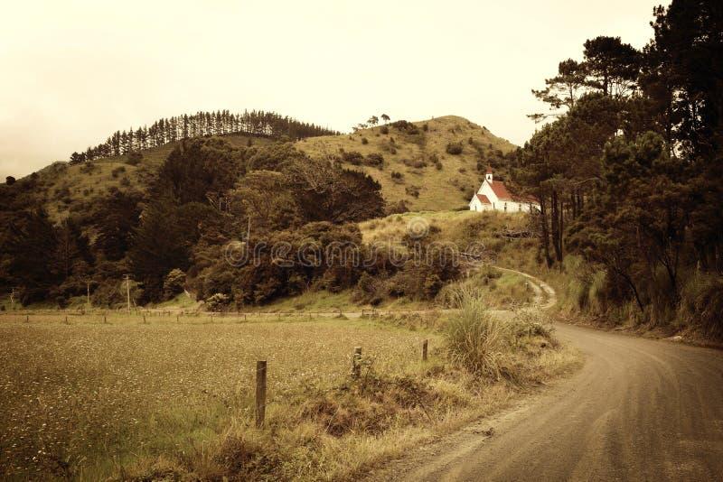 Un vicolo serpeggiante del paese circondato dai campi, erba, colline ed alberi, con una Camera della scuola fotografie stock
