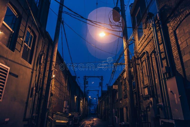 Un vicolo terrificante tenue acceso con il chiarore ed il cielo blu leggeri fotografia stock libera da diritti