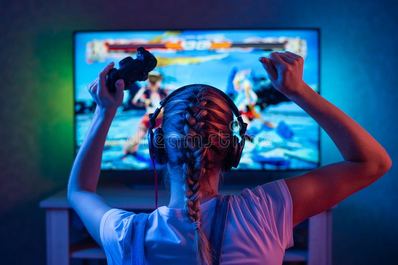 Un videojugador o una muchacha de la flámula en casa en un cuarto oscuro con un gamepad que juega con los amigos en las redes en  foto de archivo