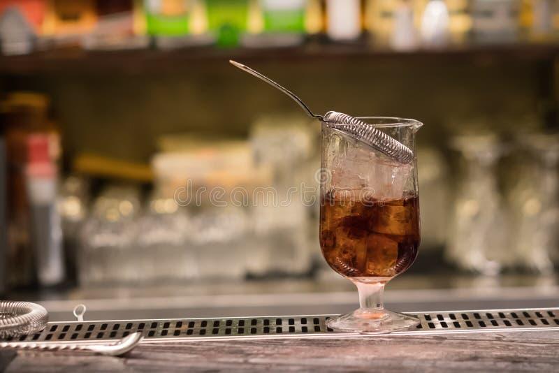 Un vidrio con el cóctel alcohólico que se coloca en contador de la barra Proceso de mezcla de la bebida del alcohol Tendencias mo imagen de archivo