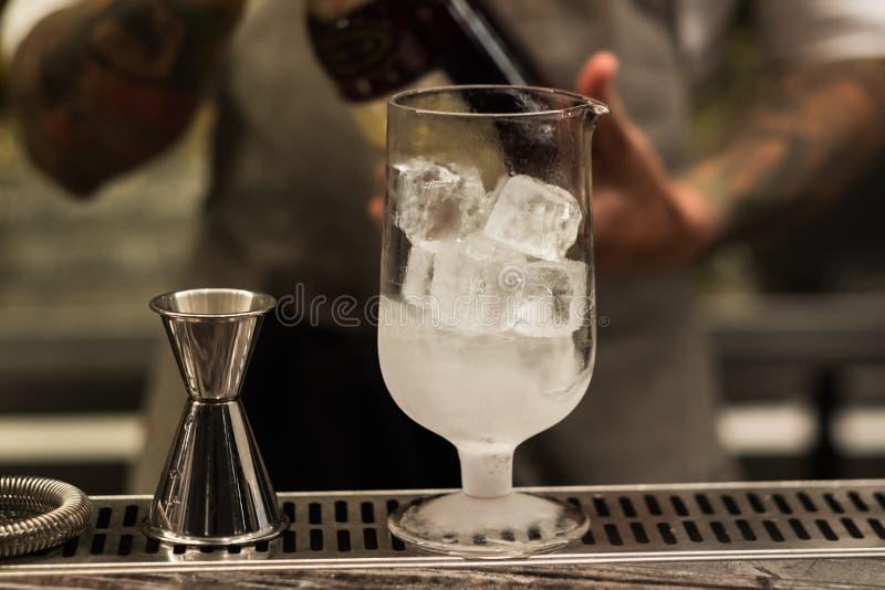 Un vidrio con el cóctel alcohólico que se coloca en contador de la barra Proceso de mezcla de la bebida del alcohol Tendencias mo fotografía de archivo libre de regalías