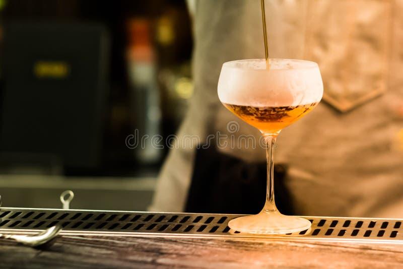 Un vidrio con el cóctel alcohólico que se coloca en contador de la barra Proceso de mezcla de la bebida del alcohol Tendencias mo foto de archivo libre de regalías