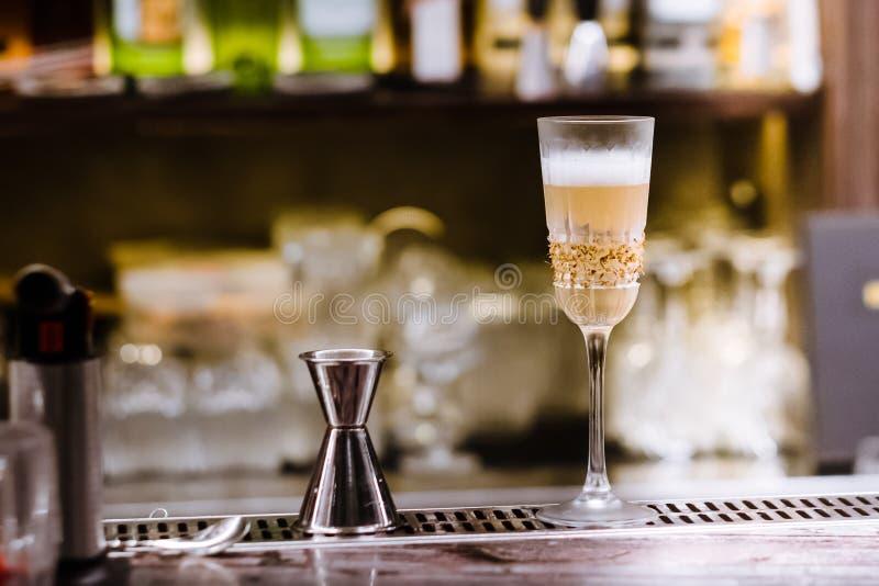 Un vidrio con el cóctel alcohólico que se coloca en contador de la barra Proceso de mezcla de la bebida del alcohol Tendencias mo fotos de archivo