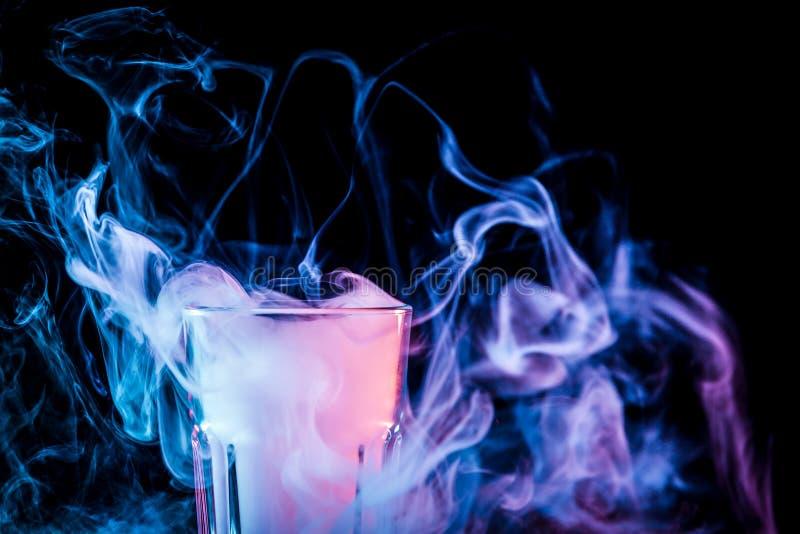 Un vidrio con humo colorido imagen de archivo