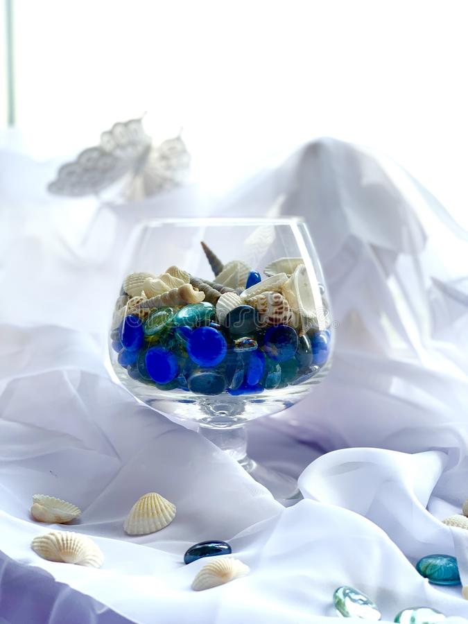 Un vidrio con las piedras del mar, cáscaras, turquesa azul, color plata En un fondo blanco Decoraci?n del mar fotos de archivo libres de regalías