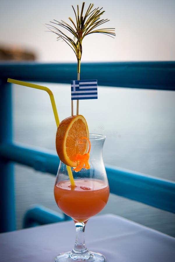 Un vidrio con una naranja y un cóctel y con una bandera griega se coloca en una tabla en un café imágenes de archivo libres de regalías