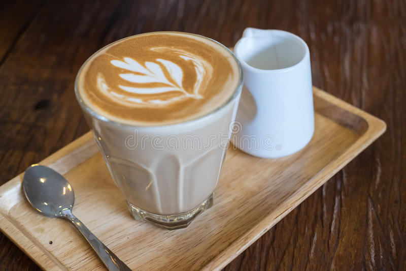 Un vidrio de café de flautín caliente del latte en la bandeja de madera imagen de archivo