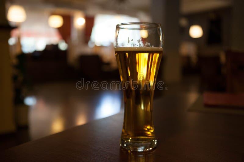 Un vidrio de cerveza en la tabla de la esquina en el restaurante imagen de archivo