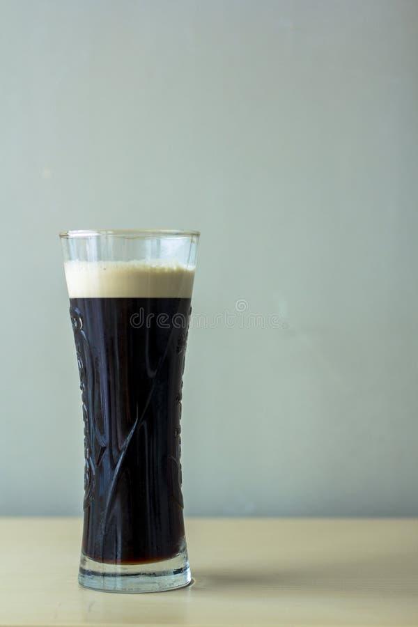 Un vidrio de cerveza oscura vida inmóvil minimalistic de una taza de cerveza oscura imagen de archivo libre de regalías