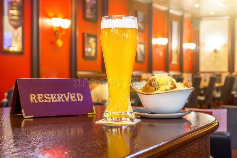 Un vidrio de cerveza sin filtro con queso de los bizcochos tostados, una tableta - es reservado en una tabla de madera en la barr foto de archivo libre de regalías