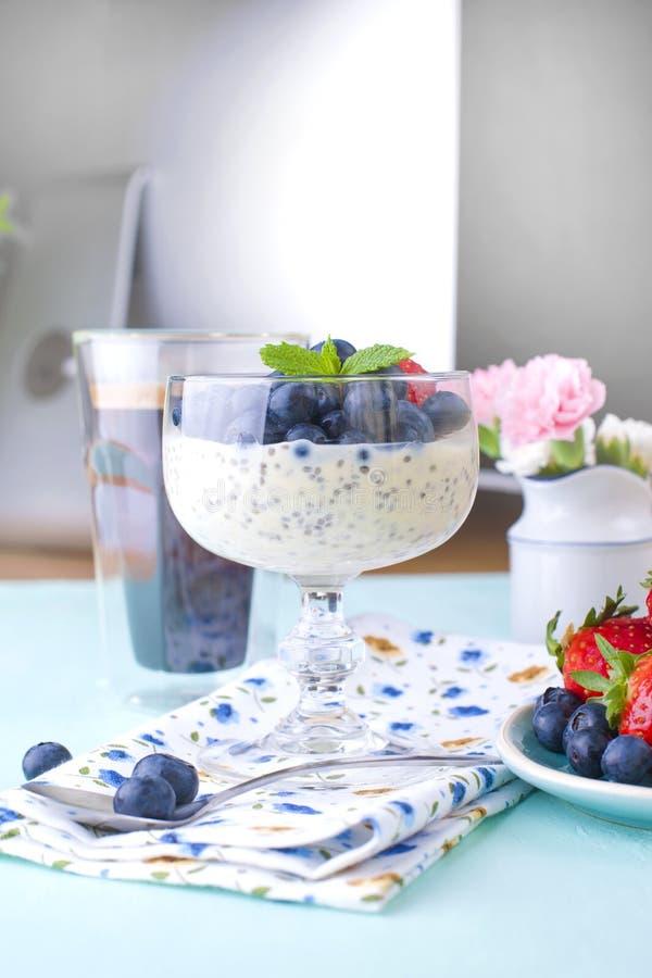 Un vidrio de chia del café y del pudín con los arándanos y las fresas para la comida sana vegetariana del desayuno Las flores en fotografía de archivo libre de regalías