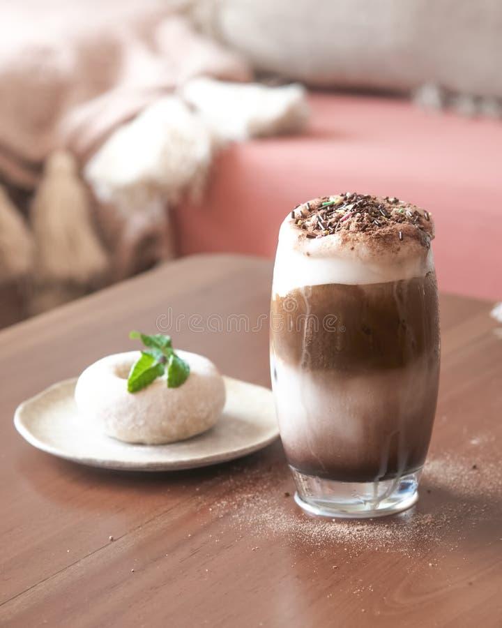 Un vidrio de chocolate con leche Frappe con crema azotada en la tabla de madera con el blanco Sugar Doughnut de la falta de defin imagenes de archivo