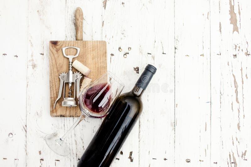 Un vidrio de corchos del vino rojo, de la botella, del sacacorchos y del vino en rusti imagen de archivo