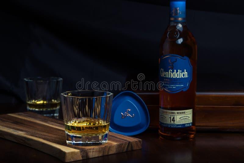 Un vidrio de escocés y una botella de whisky en una sobremesa del palo de rosa imagen de archivo libre de regalías