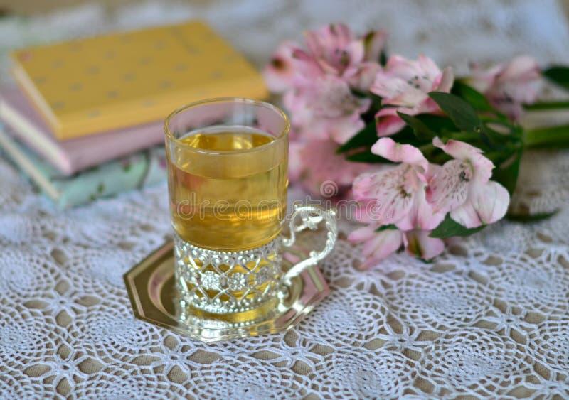 Un vidrio de infusión de hierbas en el fondo de flores y de cuadernos fotos de archivo libres de regalías