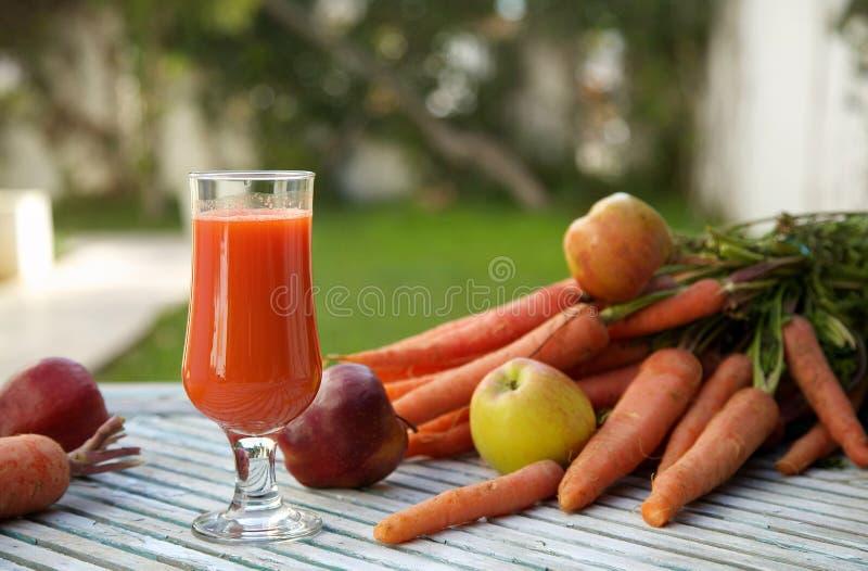 Un vidrio de jugo de zanahoria fresco de la manzana fotografía de archivo libre de regalías