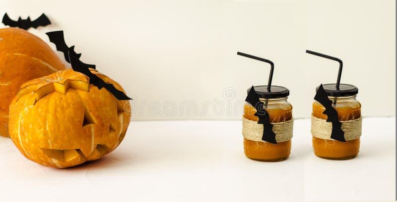 Un vidrio de jugo fresco de la calabaza, adornado para Halloween con un palo que vuela, se sirve con una paja con una linterna de fotos de archivo