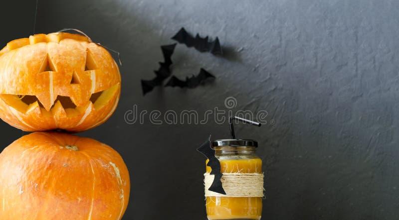 Un vidrio de jugo fresco de la calabaza, adornado para Halloween con un palo que vuela, se sirve con una paja con una linterna de fotografía de archivo libre de regalías