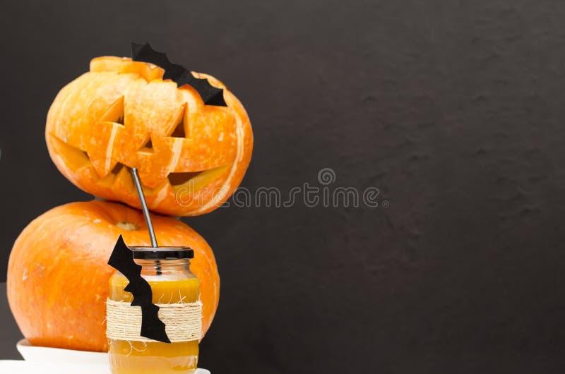 Un vidrio de jugo fresco de la calabaza, adornado para Halloween con un palo que vuela, se sirve con una paja con una linterna de fotografía de archivo