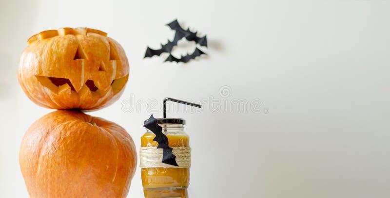 Un vidrio de jugo fresco de la calabaza, adornado para Halloween con un palo que vuela, se sirve con una paja con una linterna de fotos de archivo libres de regalías