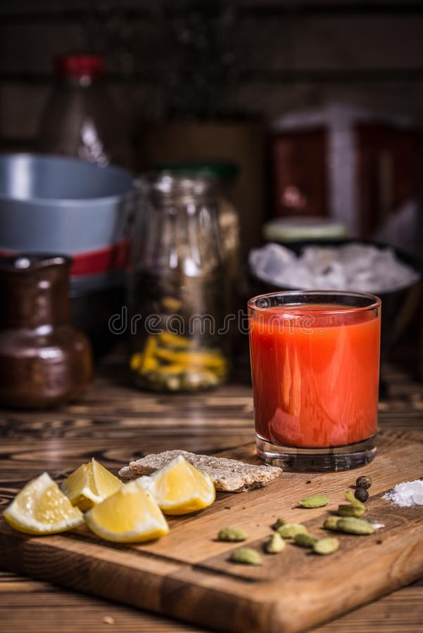 Un vidrio de jugo de tomate en un tablero de madera con las rebanadas del limón, la sal y las semillas de calabaza fotos de archivo