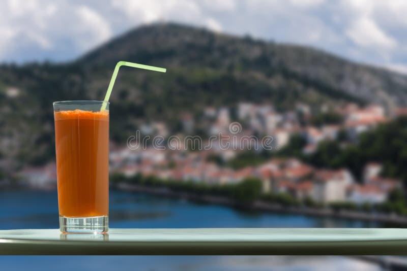 Un vidrio de jugo de zanahoria con una paja en el café en el fondo de una ciudad de Kastoria y del lago Orestias imagen de archivo libre de regalías