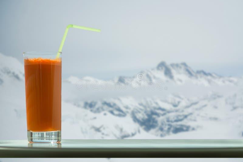 Un vidrio de jugo de zanahoria con una paja en el café en el fondo de Jungfra del glaciar en Suiza imagenes de archivo