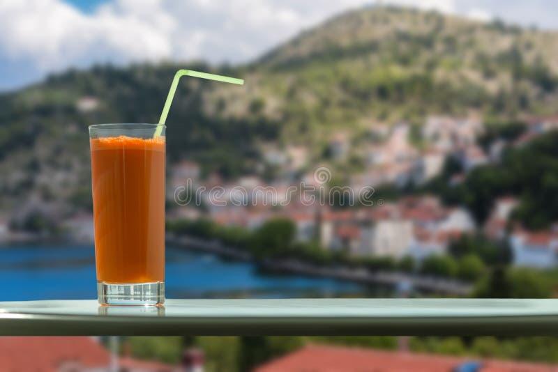 Un vidrio de jugo de zanahoria con una paja en el café en el fondo de la ciudad de Kastoria y del lago Orestias Grecia imágenes de archivo libres de regalías