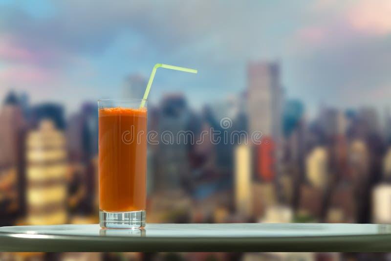 Un vidrio de jugo de zanahoria con una paja en el café en el fondo Manhattan New York City fotos de archivo